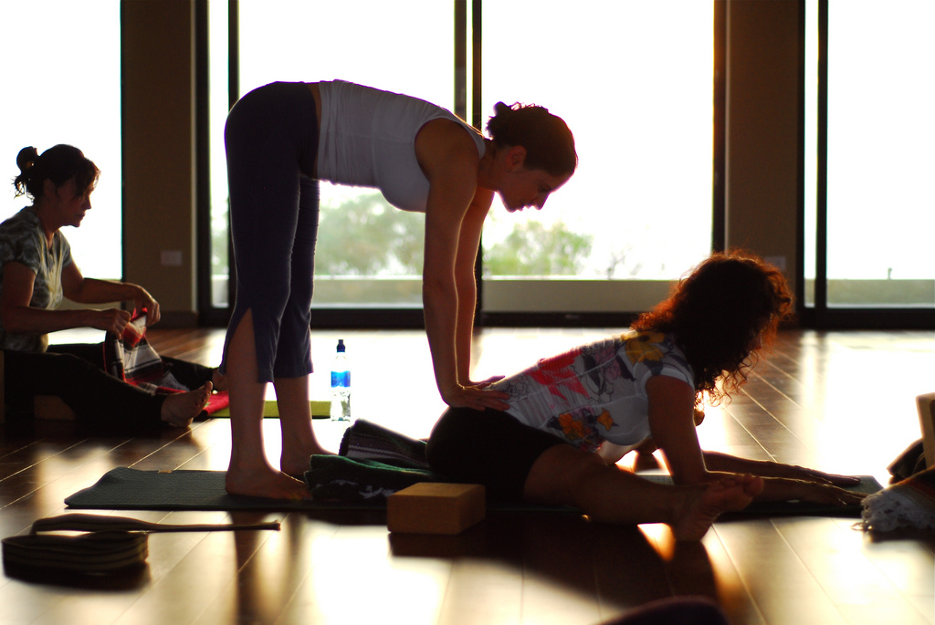 Teacher assist in restorative yoga class