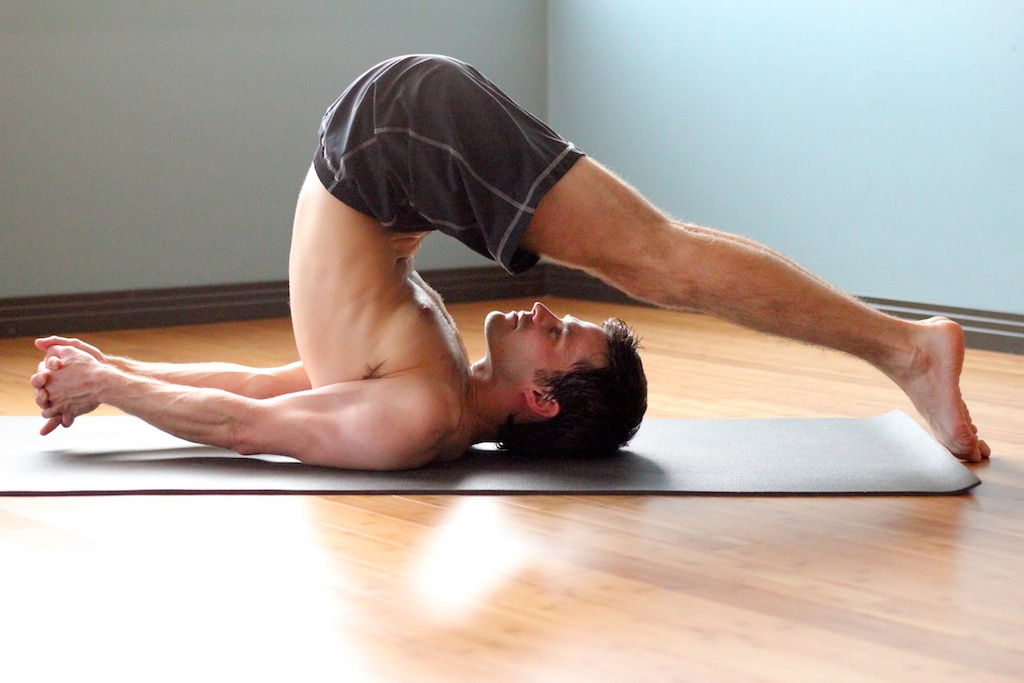 man doing yoga pose plow